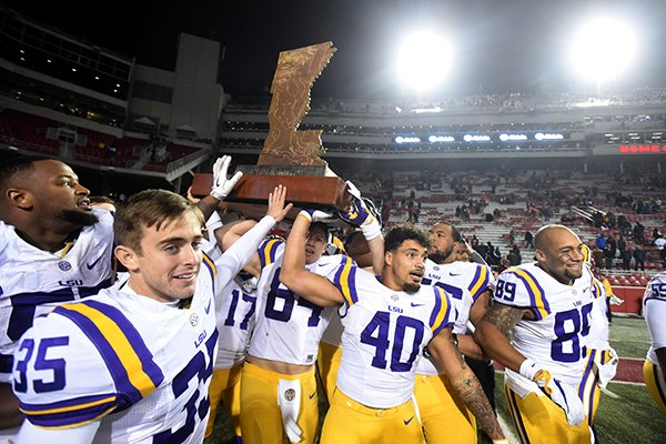 LSU players celebrate with The Boot following a 38-10 win over Arkansas on Saturday, Nov. 12, 2016, in Fayetteville.