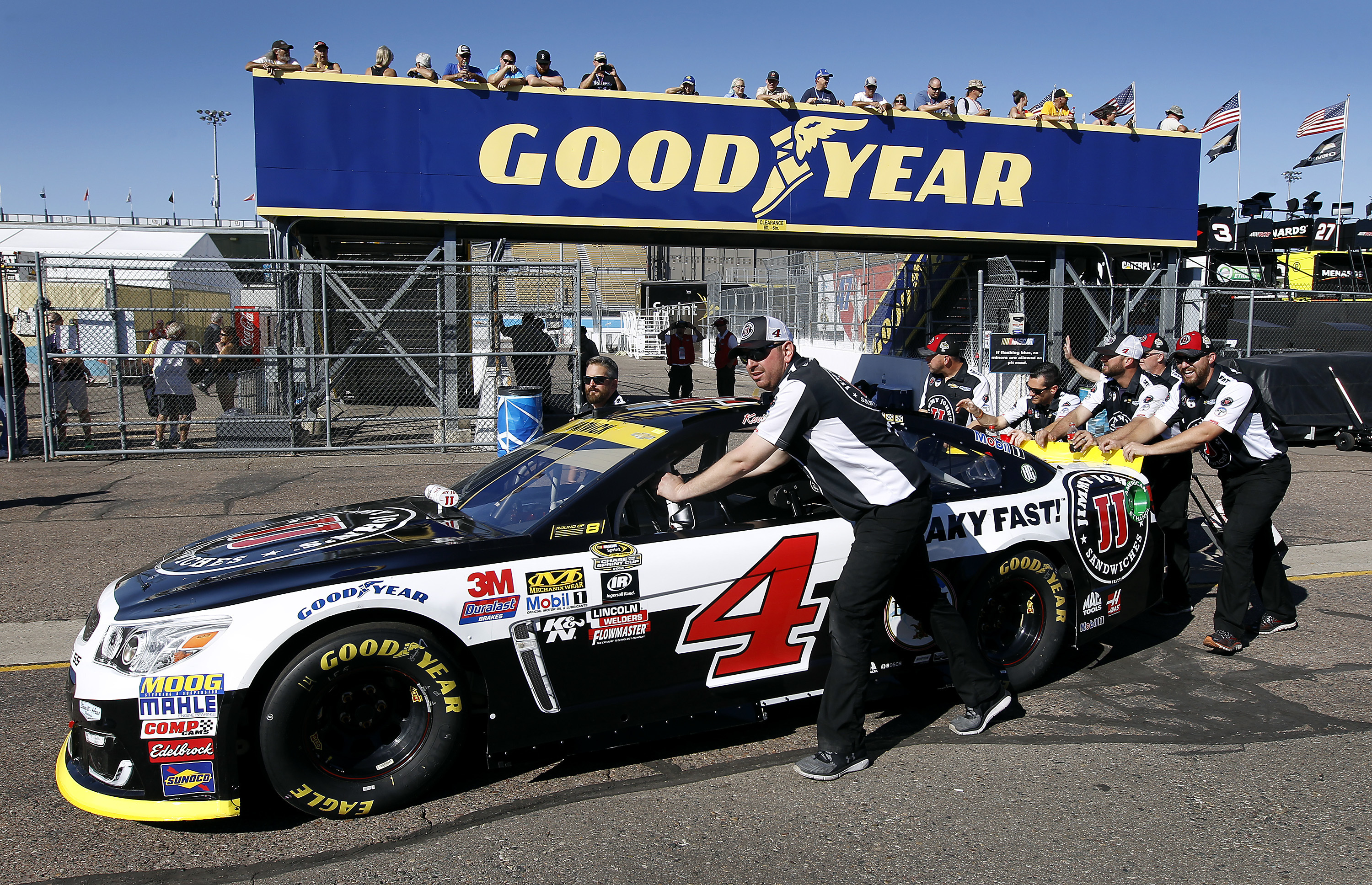 Crew members for driver kevin harvick push his car through for Garage sprint auto stains