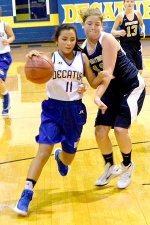 Photo by Mike Eckels Kaylee Morales (Decatur 11) dribbles around a Spartan player during the Nov. 11 Decatur-NWA Classical Academy junior high basketball game at Peterson Gym in Decatur. The junior Lady Bulldogs took victory in its second game of the season, 28 to 19.