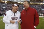 Mississippi State football coach Dan Mullen, left, and Arkansas football coach Bret Bielema confer prior to their teams meeting in an NCAA college football game in Starkville, Miss., Saturday, Nov. 1, 2014. (AP Photo/Rogelio V. Solis)