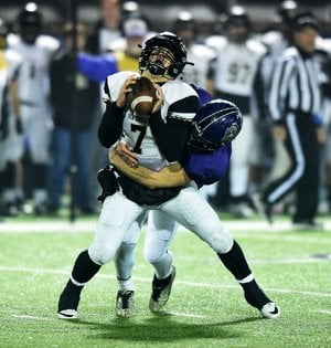 Fayetteville's Nick Scales sacks Bentonville quarterback Cannan Ross during Friday night's Class 7A playoff game at Fayetteville. The Bulldogs will play North Little Rock in the Class 7A championship game next Friday.