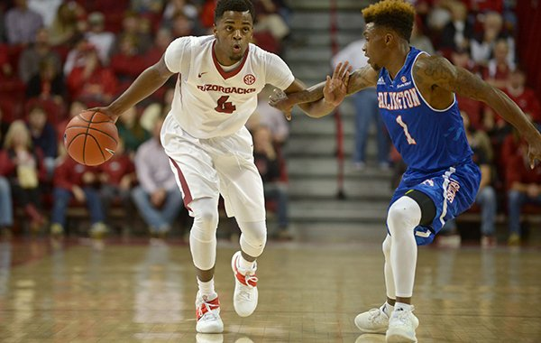 Daryl Macon (4) of Arkansas drives past Erick Neal of UT Arlington on Friday Nov. 18, 2016 during the game in Bud Walton Arena in Fayetteville.