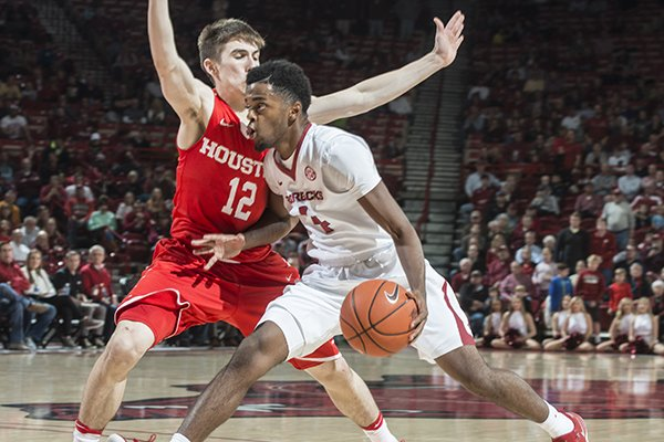 Arkansas' Daryl Macon drives past Houston's Wes Vanbeck during a game Tuesday, Dec. 6, 2016, in Fayetteville.