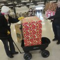 Volunteers, including Albin (from left) and Pam Rapp deliver gifts Friday during Sharing & Caring at...
