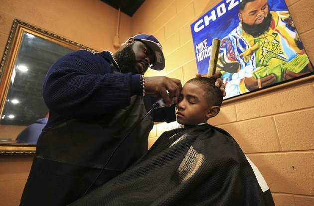 barber-mike-hutchins-gives-xavion-toliver-7-a-trim-at-fly-societe-barbershop-in-little-rock-during-wednesdays-haircut-event-for-boys-from-the-our-house-shelter