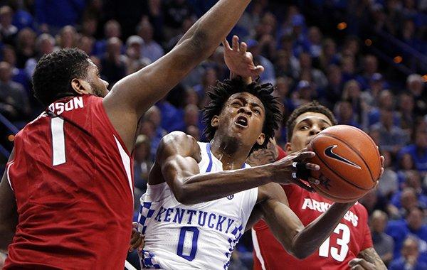 Kentucky's De'Aaron Fox (0) shoots between Arkansas' Trey Thompson (1) and Dustin Thomas (13) during the second half of an NCAA college basketball game, Saturday, Jan. 7, 2017, in Lexington, Ky. (AP Photo/James Crisp)