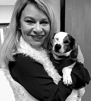 Submitted photo Lakeside Middle School Principal Jamie Preston recently befriended a blind dog rescued by the Humane Society of Garland County. Students volunteered at the Humane Society for the school's annual Day of Caring and met a number of dogs ready for adoption.