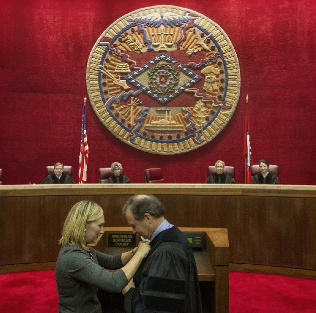 arkansas-supreme-court-chief-justice-dan-kemp-is-robed-by-his-daughter-erin-brogdon-during-an-oath-of-office-ceremony-in-2017-in-the-courtroom