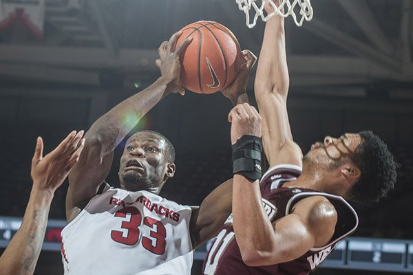 Arkansas' Moses Kingsley (33) comes down with a rebound against Mississippi State's Quinndary Weatherspoon during a game Tuesday, Jan. 10, 2017, in Fayetteville.