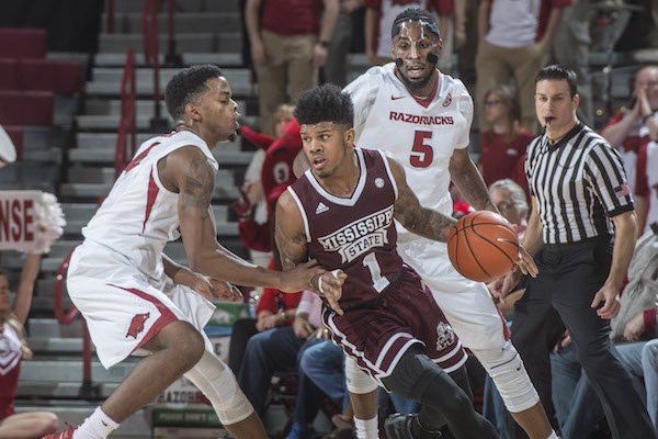Mississippi State's Lamar Peters surveys the floor while being guarded by Arkansas' Daryl Macon in the Bulldogs' 84-78 win in Bud Walton Arena on Tuesday, Jan. 10, 2017.