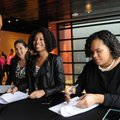 A guest is welcomed Saturday by Gina Allgaier (from left), Jazmine Harbin and Ronniesha Forrest to a...