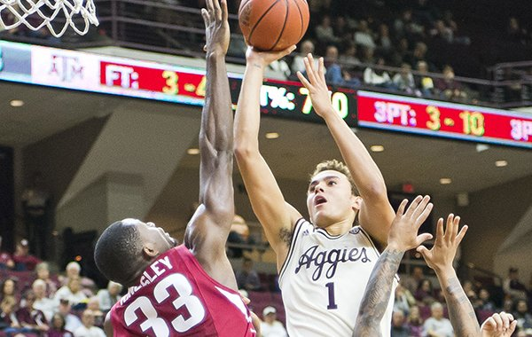 Texas A&M forward D.J. Hogg (1) puts a shot up over Arkansas forward Moses Kingsley (33) and guard Anton Beard (31) during an NCAA college basketball game, Tuesday, Jan. 17, 2017 at Reed Arena in College Station, Texas. (Timothy Hurst/College Station Eagle via AP)