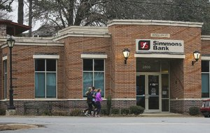 Joggers pass a Simmons Bank branch at 2800 Kavanaugh Blvd. on Wednesday. The bank is one of three Arkansas-based banks with plans to grow this year through acquisitions.