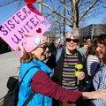 Paula Matthews (from left), greets friends Peggy Konert and Kim Stauss on Friday as hundreds demonst...