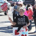 Claire Cosmos crosses the intersection at College Avenue and Dickson Street on Friday as hundreds de...
