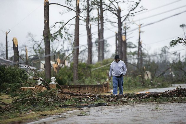 mike-jones-walks-monday-through-an-albany-ga-neighborhood-that-was-damaged-by-a-tornado