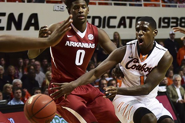 Oklahoma State's Jawun Evans throws a pass past Arkansas' Jaylen Barford during an NCAA college basketball game in Stillwater, Okla., Saturday Jan. 28, 2017. (Tyler Drabek/Tulsa World via AP)