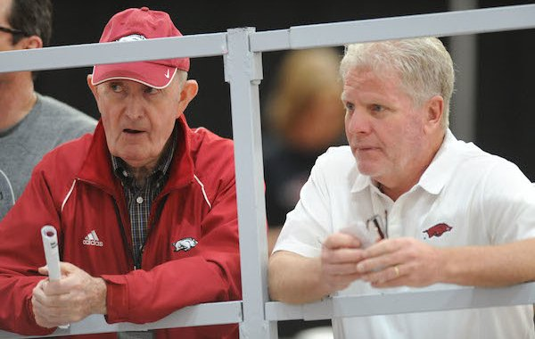 Former Arkansas coach John McDonnell (left) and current coach Chris Bucknam speak Saturday, Feb. 11, 2017, during the Tyson Invitational in the Randal Tyson Track Center in Fayetteville.