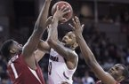 South Carolina guard Sindarius Thornwell (0) drives to the hoop against Arkansas forward Trey Thompson (1) and Manuale Watkins (21) during the first half of an NCAA college basketball game, Wednesday, Feb. 15, 2017, in Columbia, S.C. (AP Photo/Sean Rayford)
