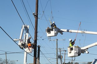 The Sentinel-Record/Richard Rasmussen POLE DAMAGED: Entergy Arkansas Inc. linemen work to restore power in the 100 block of Albert Pike Road near Anna Street intersection Thursday after a van struck a utility pole following a chase earlier in the morning.