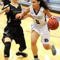Ashley Breathitt (right) of Fayetteville drives to the basket as Krista Clark of Bentonville defends...