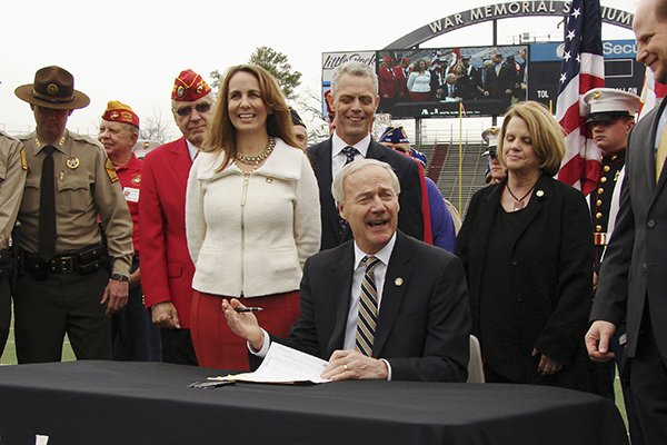 Arkansas Gov. Asa Hutchinson signs a bill on the field at War Memorial Stadium on Wednesday, Feb. 22, 2017, in Little Rock placing the stadium under the control of the state Parks and Tourism Department.