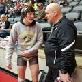 Bentonville assistant wrestling coach Bill Desler (right) talks to his son, Nathan, before one of hi...