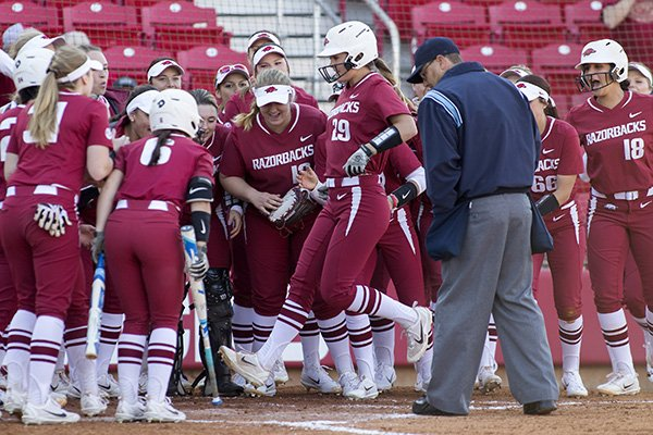 Arkansas players congratulate Nicole Schroeder (29) as she crosses the plate Friday, March 3, 2017, after Schroeder's two-run home run in the fourth inning against Nebraska at Bogle Park in Fayetteville.