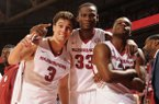 Arkansas seniors Dusty Hannahs (3), Moses Kingsley (33) and Manuale Watkins celebrate in the closing seconds against Georgia Saturday, March 4, 2017, during the second half of play in Bud Walton Arena in Fayetteville.