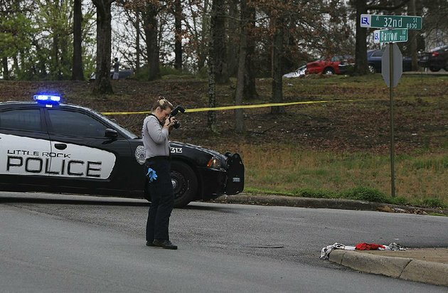 little-rock-police-department-crime-scene-investigator-photographs-the-scene-of-a-shooting-monday-afternoon-at-west-32nd-street-and-barrow-road-one-person-was-critically-injured-in-the-shooting-that-occurred-about-1145-am