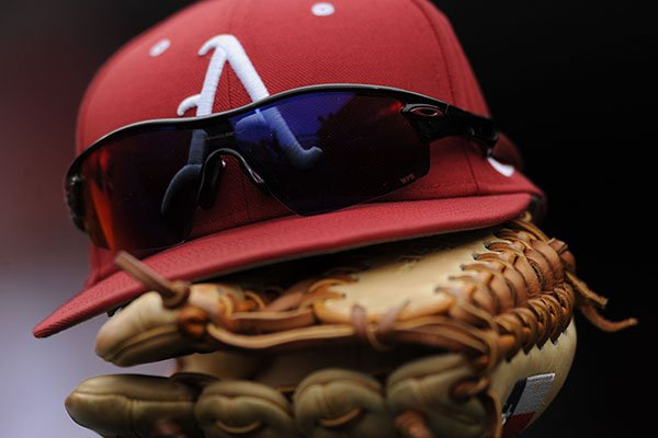 An Arkansas baseball hat and glove sit in the dugout prior to a game against Miami (Ohio) on Friday, Feb. 17, 2017, at Baum Stadium in Fayetteville.