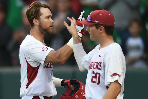 Arkansas left fielder Luke Bonfield (17) is congratulated at the plate by third baseman Carson Shaddy Friday, March 17, 2017, after hitting a 2-run home run scoring Chad Spanberger during the first inning against Mississippi State at Baum Stadium in Fayetteville.