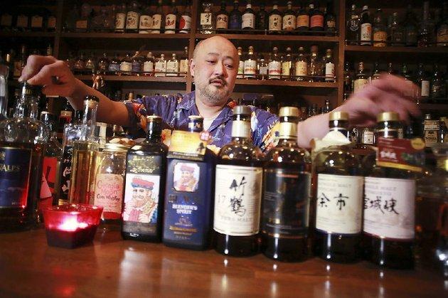 shot-bar-zoetropes-owner-and-bartender-atsushi-horigami-adjusts-the-bottles-of-japan-made-whisky-at-his-bar-in-tokyo