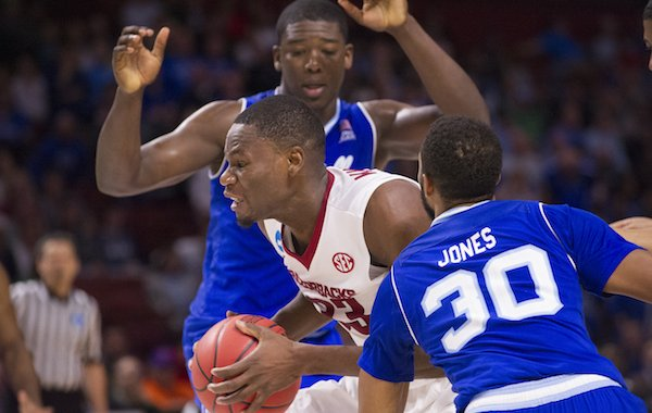 Arkansas' Moses Kingsley drives to the basket between Seton Hall's Angel Delgado and Madison Jones (30) Friday Mar. 17, 2017 during the first round of the NCAA Tournament at the Bon Secours Wellness Arena in Greenville, South Carolina. Arkansas won 77-71 and will advance to the second round, playing Sunday at the same location.
