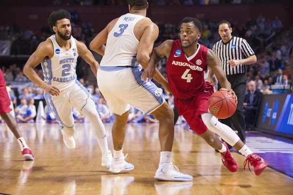 Arkansas' Daryl Macon drives around North Carolina's Kennedy Meeks Sunday March 19, 2017 during the second round of the NCAA Tournament at the Bon Secours Wellness Arena in Greenville, South Carolina.