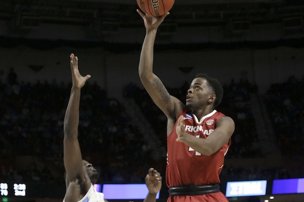 Arkansas' Daryl Macon, right, shoots over North Carolina's Theo Pinson, left, during the first half in a second-round game of the NCAA men's college basketball tournament in Greenville, S.C., Sunday, March 19, 2017. (AP Photo/Chuck Burton)