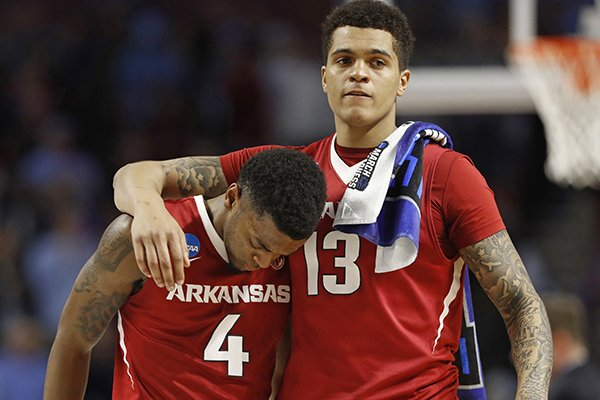 Arkansas' Daryl Macon (4) is consoled by Dustin Thomas (13) after a second-round game against North Carolina in the NCAA men's college basketball tournament in Greenville, S.C., Sunday, March 19, 2017. (AP Photo/Chuck Burton)