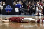 Arkansas' Dusty Hannahs lies on the court after a second-round game against North Carolina in the NCAA men's college basketball tournament in Greenville, S.C., Sunday, March 19, 2017. (AP Photo/Rainier Ehrhardt)