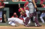 Arkansas' Jordan McFarland slides past Mississippi State catcher Dustin Skelton Sunday, March 19, 2017, for a run at Baum Stadium in Fayetteville.