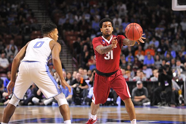 Arkansas guard Anton Beard passes the ball during a game against North Carolina on Sunday, March 19, 2017, in Greenville, S.C.