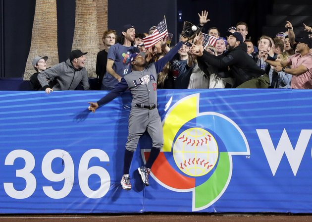 us-outfielder-adam-jones-grabs-a-catch-above-the-wall-for-the-out-on-the-dominican-republics-manny-machado-during-the-seventh-inning-of-a-second-round-world-baseball-classic-baseball-game-saturday-march-18-2017-in-san-diego