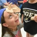 """Macie Davis, 7, delights in """"being a unicorn"""" Tuesday during an art project at Adventure Club spring..."""