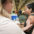 Janeth Abarca of Rogers gets a measles-mumps-rubella vaccine shot from nurse practitioner Heron Mart...