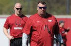 Arkansas coach Bret Bielema (right) watches Saturday, April 1, 2017, as head strength and conditioning coach Ben Herbert leads warmup drills during practice at the university practice field in Fayetteville.