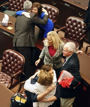 Lawmakers embrace on the fl oor of the House on Monday after Speaker Jeremy Gillam, R-Judsonia, gaveled the 91st General Assembly into recess. The next meeting will be May 1, when the session is to officially adjourn.