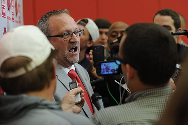 Arkansas women's basketball coach Mike Neighbors (left) speaks Tuesday, April 4, 2017, with members of the media during a ceremony and press conference to announce his hire at the university's basketball practice facility.