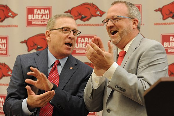 Jeff Long (left), director of athletics at the University of Arkansas, speaks with newly hired Arkansas women's basketball coach Mike Neighbors Tuesday, April 4, 2017, during a ceremony and press conference to announce his hire at the university's basketball practice facility.