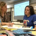 English teacher Cristina Cox (left) gives seventh-grader Savannah Robinson, 13, some tips on writing...