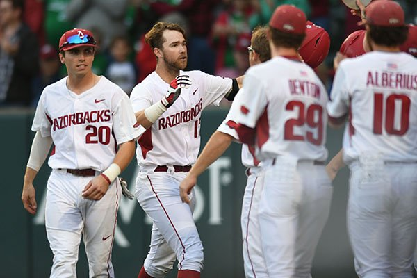 Arkansas left fielder Luke Bonfield (center) is congratulated at the plate by teammates Friday, March 17, 2017, after hitting a 2-run home run scoring Chad Spanberger during the first inning against Mississippi State at Baum Stadium in Fayetteville. Visit nwadg.com/photos to see more photographs from the game.