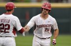 Chad Spanberger (24), Arkansas first baseman, shakes assistant coach Tony Vitello's hand as he rounds third base after hitting a home run Thursday, April 13, 2017, during the first inning against Georgia at Baum Stadium in Fayetteville.